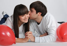 Charming love couple lying on the floor. Young man kiss pretty young woman Stock Photo
