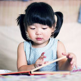 Charming and lovely asian kid reading book.  Royalty Free Stock Photos