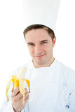Charming male cook holding a banana and smiling Stock Photography
