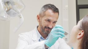 Charming male dentist smiling to the camera while working with patient stock footage