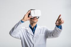 Charming male doctor switching images in VR glasses. Progress in medicine. Adorable appealing male doctor amplifying VR glasses  image while  examining table and Royalty Free Stock Photography