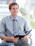 Charming male executive looking at his agenda Stock Image