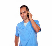 Charming male nurse talking on cellphone. Portrait of a charming male nurse talking on cellphone on white background Stock Photography