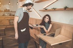 Charming male worker serving cake to customer in cafe. This is for you. Cheerful waiter is flirting with client while giving plate of dessert to her. Woman is Royalty Free Stock Images