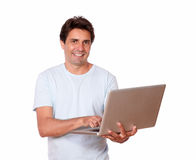 Charming male working on laptop while standing. Portrait of a charming male working on laptop while standing on white background Stock Photos