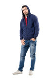 Charming man in blue hooded sweatshirt with hands in pockets looking at camera. Stock Photos