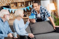 Charming man giving a present to his senior mother. Pleasant surprise. Charming young men giving a birthday present to his elderly mother sitting on the sofa Stock Image
