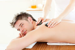 Charming man having a back massage with hot stone. In a spa centre royalty free stock photos