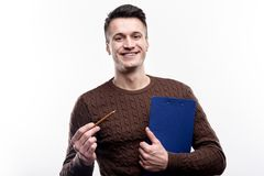 Charming man holding sheet holder and pencil. Pleasant office worker. Handsome young man in a brown sweater posing for the camera and smiling while holding a royalty free stock photo