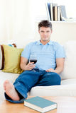 Charming man holding a wineglass on the sofa Royalty Free Stock Photography