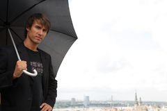 Charming man looking up with black umbrella Stock Photo
