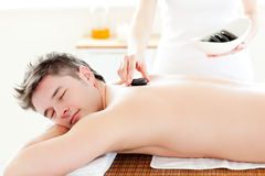 Charming man receiving a massage with hot stones Stock Image