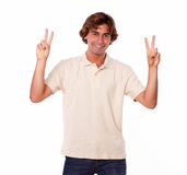 Charming man showing victory sign with fingers Royalty Free Stock Photos