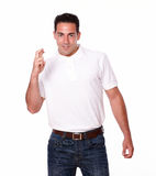 Charming man smiling and crossing fingers Royalty Free Stock Image
