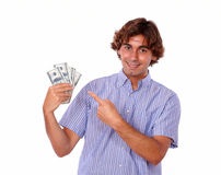 Charming man smiling and pointing to cash dollars. Royalty Free Stock Images