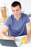 Charming man using his laptop holding orange juice Royalty Free Stock Photos