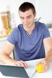 Charming man using his laptop holding orange juice Royalty Free Stock Photos
