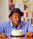 Charming man wearing blue shirt and hat sitting by table with birthday cake in front, blowing candles celebrating alone Stock Photos