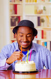 Charming man wearing blue shirt and hat sitting by table with birthday cake in front, touching candle celebrating alone Royalty Free Stock Photo