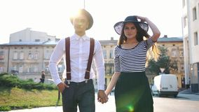 Charming man and woman in black hats walk along the street on the sunset stock footage