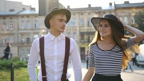 Charming man and woman in black hats walk along the street on the sunset stock video