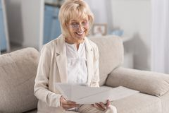 Charming mature businesswoman working with documents. Important documentation. Joyful glad mature businesswoman wearing glasses while examining papers and Stock Photos