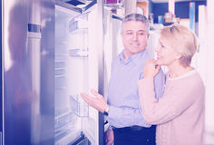 Charming mature married couple choose for themselves refrigerato Stock Image