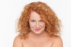 Charming mature woman. Portrait of charming mature womansmiling for camera isolated on white. Red haired lady, aged 40, posing in studio. Emotions concept Royalty Free Stock Images