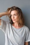 Charming mid adult woman posing with hand in hair Royalty Free Stock Images
