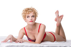 Charming middle-aged blonde lying in bed Stock Photos