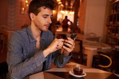 Charming millenial texting in a restaurant. Charming millenial sitting at table in restaurant texting with concentration on his cell phone with a cup of tea on Stock Photography