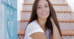 Charming model in casual outfit posing on painted stairs stock footage