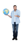 Charming model holding a globe and shrugging shoulders Stock Image