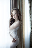 Charming model posing at window in hotel room Stock Images