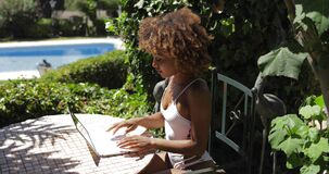 Charming model relaxing with laptop in poolside stock video
