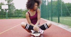 Charming model sitting on skateboard stock video