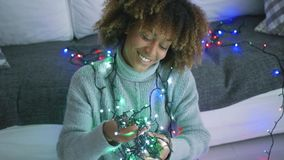 Charming model with twinkle lights. Portrait of adorable young woman posing at home in sweater holding plenty of glowing lights of garland smiling at camera stock video footage