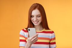 Free Charming Modern Redhead Girl College Student Checking Message Box Holding Smartphone Look Happy Smiling Delighted Royalty Free Stock Image - 214336296