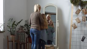 Charming mom and daughter doing makeup at home stock video