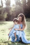 Charming mom with small daughter in blue long sitting on the gra Stock Photography