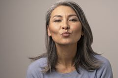Charming Mongolian Woman with Gray Hair Over a Gray Background. stock photos