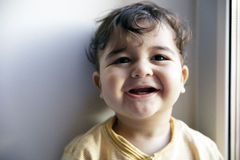 Charming 8 months old baby boy looking cheerful. And laugh near the window. Selective soft focus Royalty Free Stock Photo