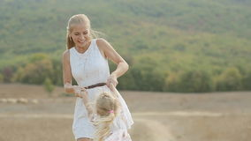 Charming mother circling happy little daughter in stock footage