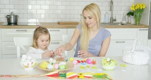 Charming mother and daughter coloring eggs stock footage