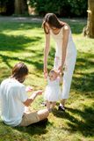 Charming mother and happy dad are teaching their little daughter wearing white dress how to make her first steps. stock photo