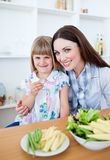 Charming mother and her daughter in the kitchen Stock Photos