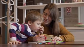 Charming mother and her little son are watching together a funny cartoon. On a smartphone. The concept of understanding between children and adults stock footage