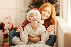 Charming mother hugging her son tightly on sofa. Cannot keep my emotions inside. Selective focus on an extremely happy child getting excited while sitting next Royalty Free Stock Photos