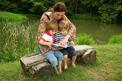 Charming Mother Reading a Book to Her Adorable Little Twin Sons While Sitting Outside  Near Beautiful Lake Stock Photography