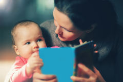 Charming mother showing images in a book to her cute little baby Stock Photos